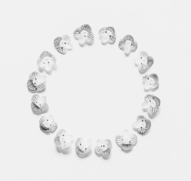 Round vintage frame of small flowers on a white  with space for text, black and white  . flat lay, top view
