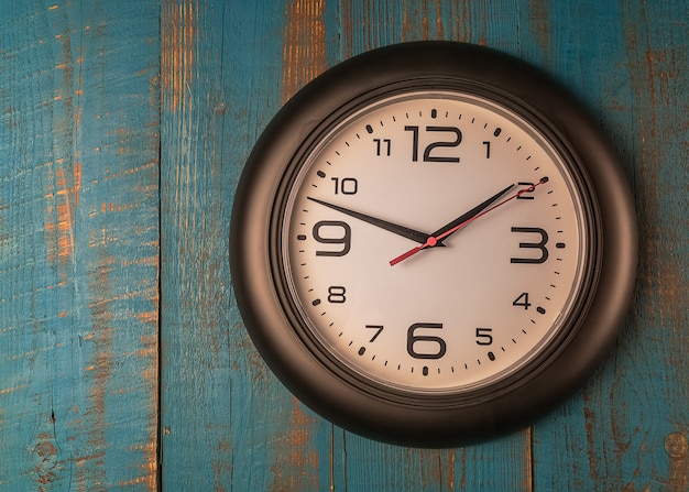Round wall clock against old wooden blue table.