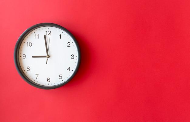 9を示す赤い表面の丸い壁時計