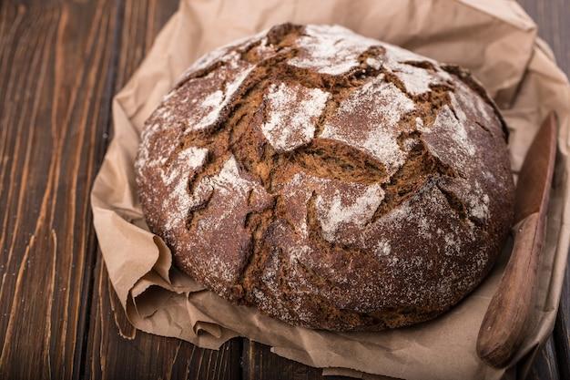 Круглый теплый свежий хлеб на старом деревянном столе и на бумаге