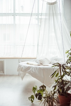 Round white bed with cushions suspended in the house