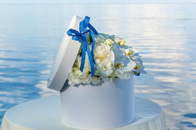 꽃과 파란색 활이 있는 둥근 흰색 상자는 바다 배경에 있는 탁자 위에 서 있습니다.
