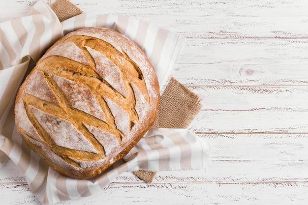Round white bread on cloth in kitchen