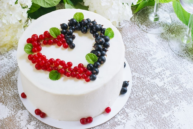 Round white cake with berries in the form of hearts, valentine's day, on white surface. picture for a menu or a confectionery catalog. top view