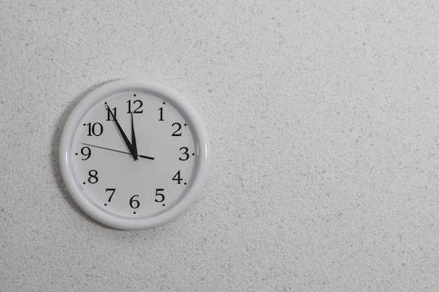 가벼운 질감의 벽에 손이 있는 둥근 흰색 시계. 시간을 결정하는 장치.