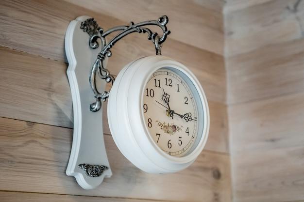 로마 숫자가 새겨진 둥근 흰색 시계는 공공 건물 벽에 측면도를 장착했습니다.