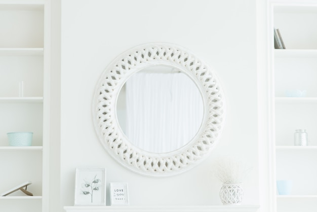Round white mirror on a light wall
