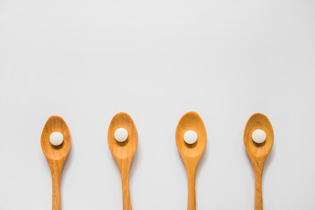 Round white pill on wooden spoons over the white background