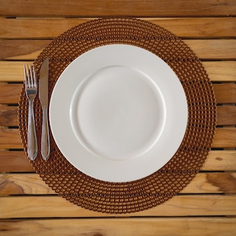 Round white plate and embase wooden cutlery. top view.