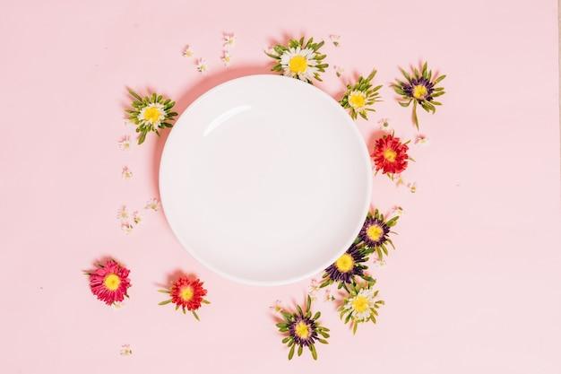 Круглая белая тарелка размещена на розовом с цветами вокруг