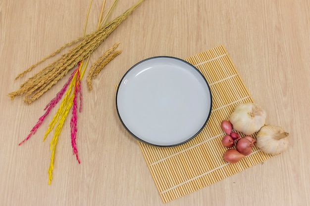 A round white plate was placed on the table, and garlic, onion, rice were placed around it.