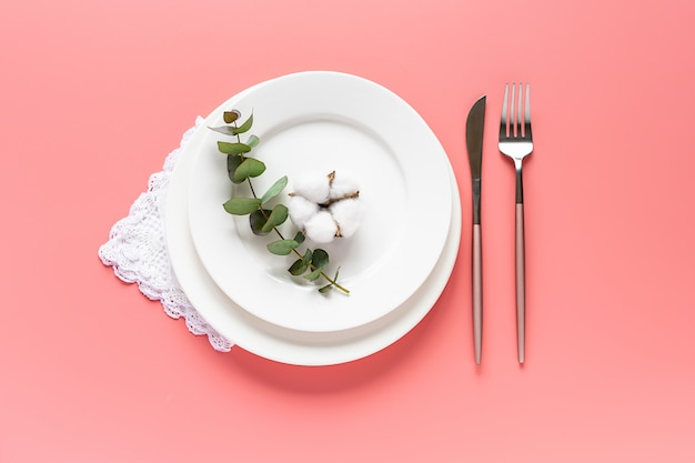 Round white plates, cutlery, vintage napkin, eucalyptus twig and cotton flower on pink pastel background.