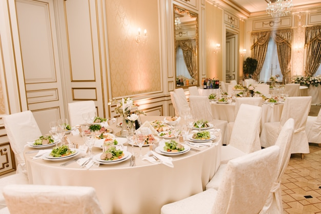 The round white table is filled with a large amount of food and various snacks in a luxurious interior, beautiful serving of the holiday table