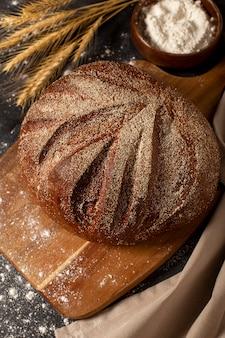Круглый цельный хлеб на деревянной разделочной доске, присыпанной мукой и колосками злаков на темном столе, вертикальное фото, свободное место для текста. фото высокого качества
