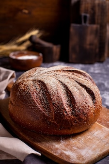 Round whole bread on a wooden cutting board sprinkled with flour and spikelets of cereals on a dark table