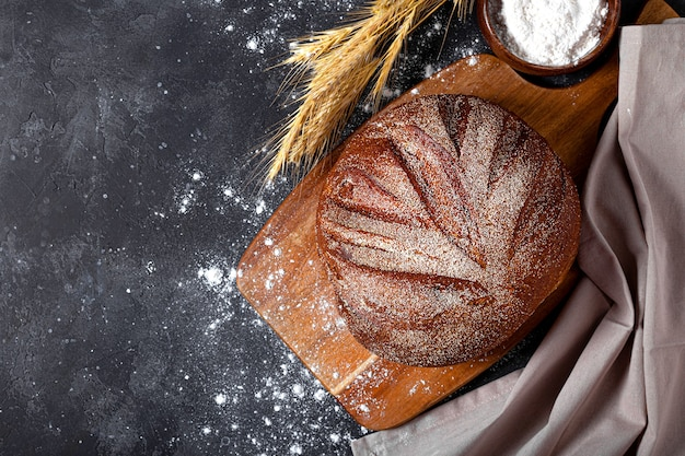 Round whole bread on a wooden cutting board sprinkled with flour and spikelets of cereals