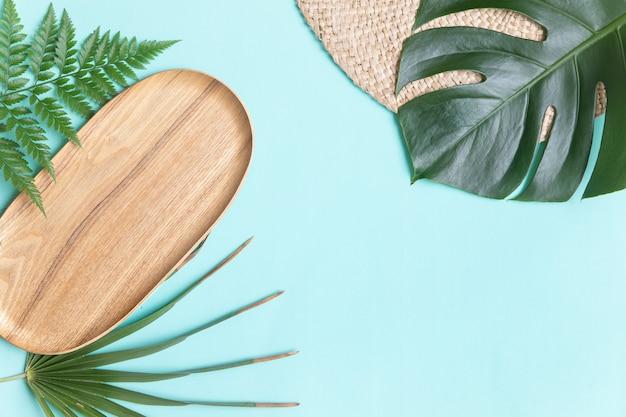Круглая плетеная подставка и пальмовые листья.