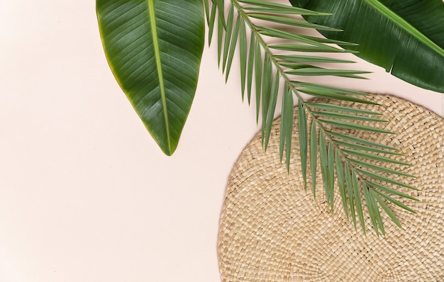 Round wicker stand and palm leaves on pink wall