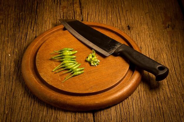 ラウンドウッドチョッピングボード。唐辛子は緑と赤です。ナイフ