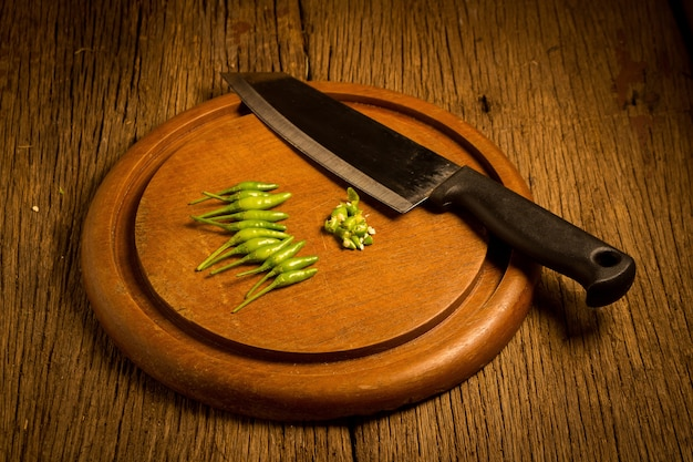 Round wood chopping cutting board. chili peppers green and red. knife