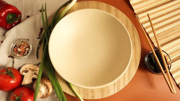 Круглая деревянная доска и тарелка, соус и различные овощи на столе,