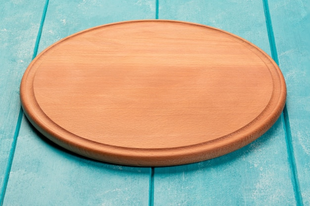 푸른 나무 테이블에 피자를 위한 둥근 나무 커팅 보드. 전체 피사계 심도. 식품 프로젝트를 위한 모형.