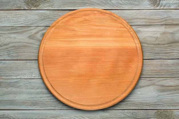 회색 나무 테이블에 피자를 위한 둥근 나무 커팅 보드. 식품 프로젝트를 위한 모형. 평면도.