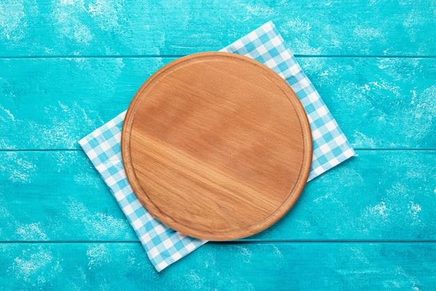 파란색 나무 테이블에 파란색 격자 무늬 식탁보가 있는 피자용 둥근 나무 커팅 보드. 평면도. 식품 프로젝트를 위한 모형.