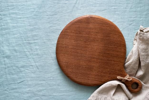 Круглая деревянная разделочная доска на синей льняной текстильной скатерти