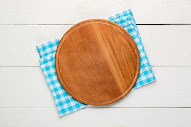 Round wooden cutting board for pizza with blue plaid tablecloth on white wooden table. top view. mockup for food project.