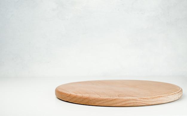 ライトグレーのテーブルにコピースペースのある丸い木製まな板