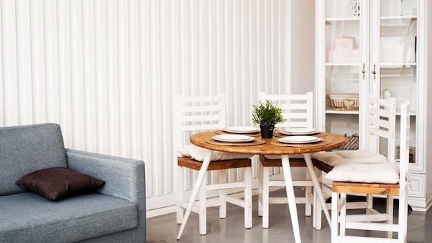 둥근 나무 식탁과 흰색 의자. 주방과 식당의 현대 스칸디나비아 인테리어.
