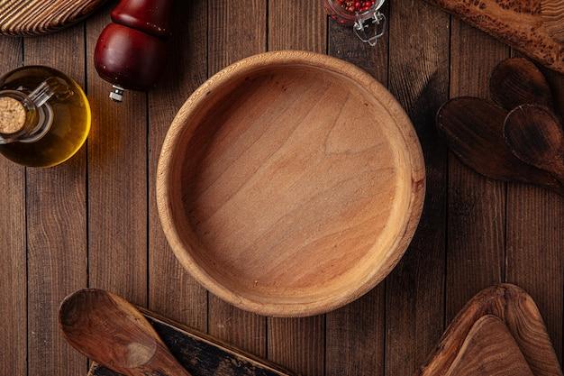 Круглая деревянная пустая миска на деревянном фоне