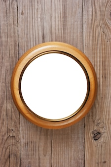 Round wooden frame on a wooden wall