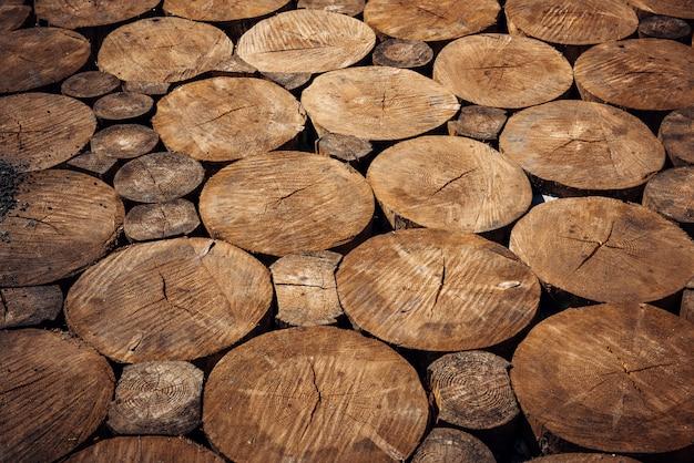 丸い木の丸太を刻んだ、歩道。製材ログ、クローズアップ。自然な木製の背景。