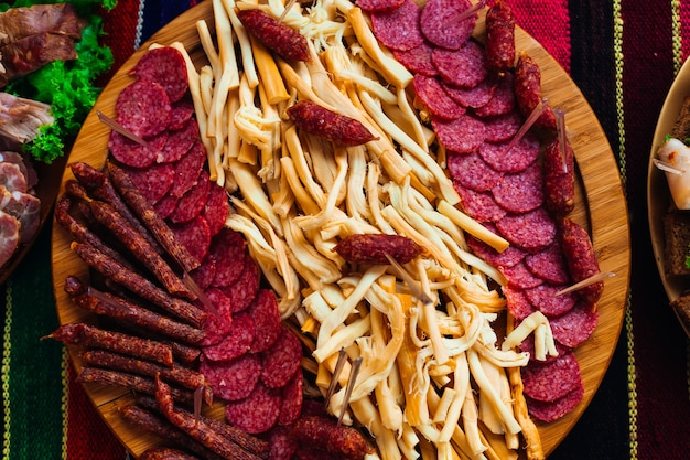 Круглая деревянная тарелка с сыром колбасы и ватой салями крупным планом