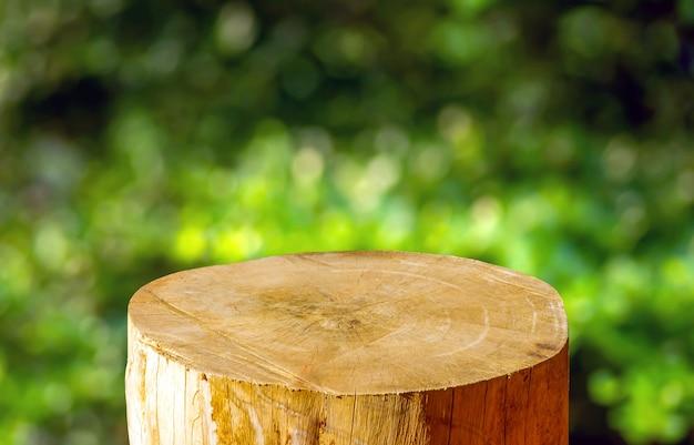 緑のボケ味の抽象的な背景を持つ製品ディスプレイ用の丸い木製のこぎりカットシリンダー形状