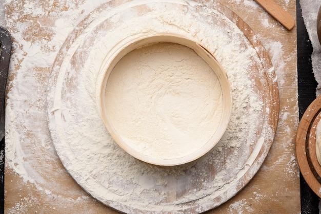 Круглое деревянное сито и белая пшеничная мука на деревянной доске, вид сверху