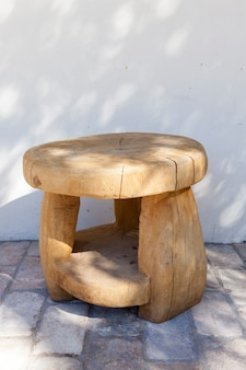 Круглый деревянный табурет, сделанный вручную из большого ствола дерева. стоит на кирпичном полу возле белого дома. на поверхности тени от растущих возле деревьев