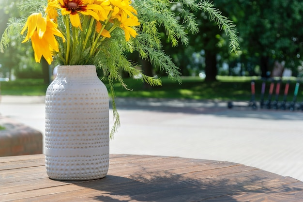 Round wooden table at street coffee shop or cafe with vase full of natural flowers against the trees in the park on a sunny summer day.
