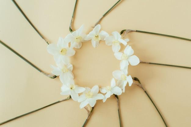 ラウンドリースフレームコピースペースモックアップ。水仙の花。フラットレイ、トップビュー花の夏のコンセプト。