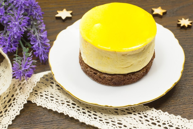 Round yellow cake on white saucer. bands and lavender on the table. icons of stars