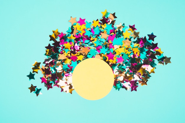 Round yellow frame surrounded with colorful star confetti on blue background