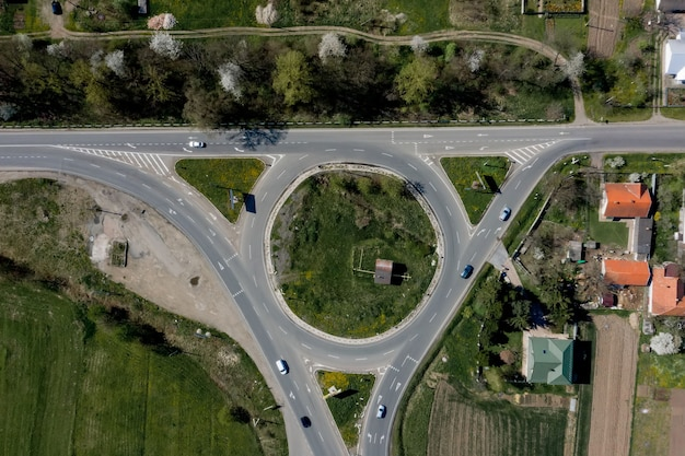 Объездное движение легковых и грузовых автомобилей на круговой кольцевой дороге с воздуха сверху. Premium Фотографии