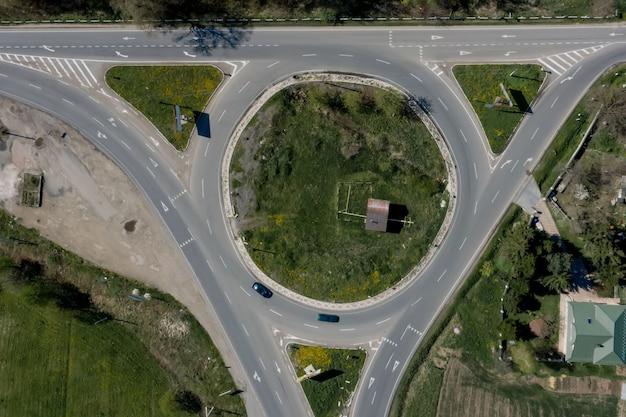 Объездное движение легковых и грузовых автомобилей на круговой кольцевой дороге с воздуха сверху.