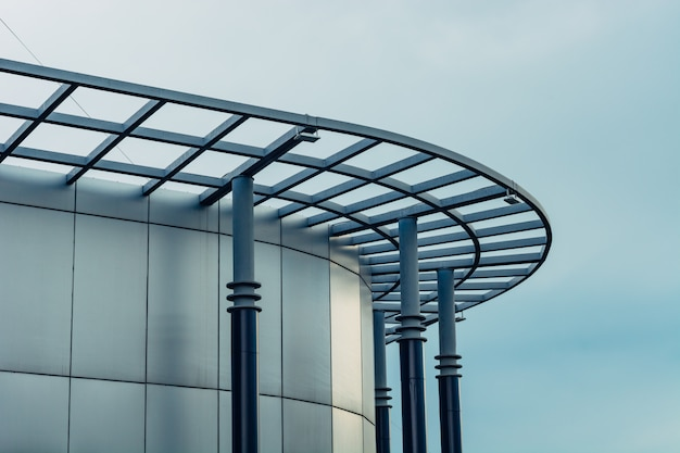 A rounded facade of a modern glass building against the sky.