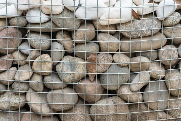 Закругленные камни за металлической сеткой Premium Фотографии