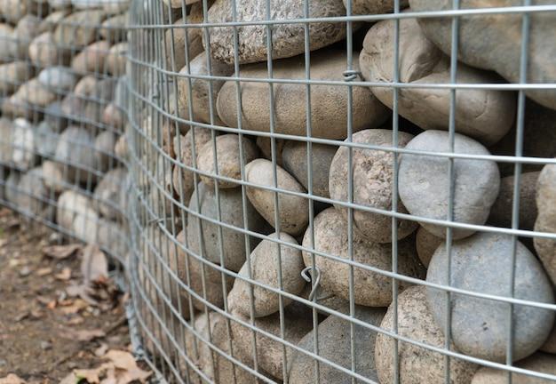 Закругленные камни за металлической сеткой