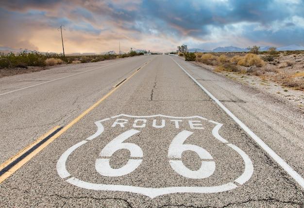Маршрут 66 дорожный знак с фоном голубого неба. историческая улица, на которой никого нет. классическая концепция для путешествий и приключений в винтажном стиле.