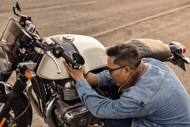 On the route to a summer vacation on a motorcycle, biker guy on an asphalt highway, a crouching motorcyclist is concerned about a motorcycle breakdown.